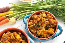 Horizontal image of a potato, carrot, and lentil stew in blue bowls with handles next to whole carrots.