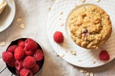 Top-down vertical image of a muffin and two raspberries on a plate, with a measuring cup of more berries, a plate of butter, and scattered oats on a beige tablecloth.