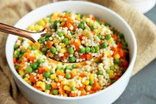 Horizontal image of a spoon holding a grain and veggie salad.
