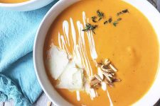 Horizontal image of carrot soup with assorted garnishes and a blue towel.