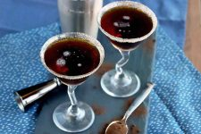 Two espresso martinis in glasses with decoratively bent stems, on a slate serving platter with a cocktail shaker and jigger, and a spoon filled with espresso powder with more scattered on the slate, on one plain blue cloth beneath a white and blue speckled patterned cloth, on a wood surface.