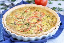 Tomato, egg, and herb tart in a white ceramic pan, on a blue cloth with scattered ingredients.