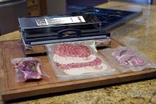 A photo of the Weston Pro 2300 vacuum sealer bagging cold cuts and other lunch meat on a large wooden cutting board.