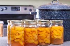 Canned Peaches with a water bath canner on counter.