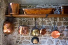 Copper Pots and Pans hanging on chateu wall in Normandy