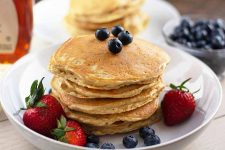 Horizontal image of a stack of flapjacks on a white dish with fresh strawberries and blueberries, with a bowl of blueberries and syrup in the background.