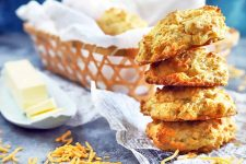 Horizontal image of a stack of four cheese drop biscuits on the right, with a basket lined with parchment filled with more of the baked goods in the background and a ceramic dish of butter to the left, on newspaper print tissue paper on a gray surface, with scattered shredded cheese.