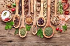 Top down view of seven wooden spoons and couple of bowls sitting on a rustic wooden table top and filled with various herbs and spices.
