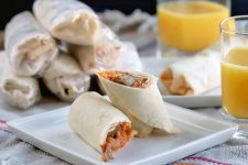 A breakfast burrito that has been cut on a diagonal is arranged with one piece stacked on top of the other for a pleasing presentation on a white, square, ceramic plate, with another identical plate in soft focus in the background beside two glasses of orange juice, and a small pyramid of six more filled tortillas wrapped in plastic, on a gray striped cloth surface with a dark brown background.