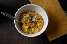 Top view of carrot risotto on a dark wooden table.