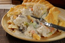 A hot chicken pot pie broken open with a fork