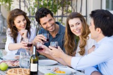 Group Of Happy Young Friends Toasting Wine Glass Outdoors at party
