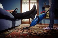 Man relaxing on couch while woman vacuums carpet