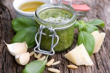 Pesto sauce on rustic wooden table with pine nuts and basil leaves scattered around