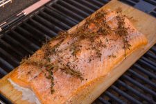 Plank that has raw salmon with dill leaves on top placed on a cedar plank which is sitting on a BBQ grill