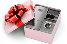 "A gift box with a a refrigerator, microwave, toaster oven, and other small kitchen appliances ""photoshopped"" into it"